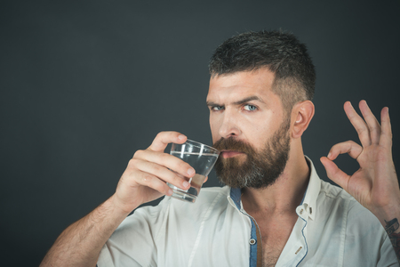 Health and dieting. Man with long beard hold water glass on grey background. Hangover and thirst. Hipster drink clean healthy water, refreshing with ok gesture. Life source and healthcare, copy space