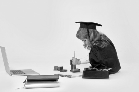 Little boy child in graduation squared cap and black mantle sitting and drawing by pencil in copy book near box with colored pencils wooden blocks diaries and open notebook isolated Imagens - 91461843
