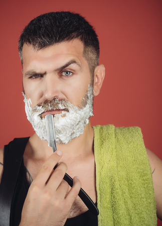 Fashion and beauty, innovation. Barber and hairdresser. Serious hipster in barbershop, new technology. Man cut beard and mustache with razor and shaving gel. Haircut of bearded man, archaism. Stock Photo