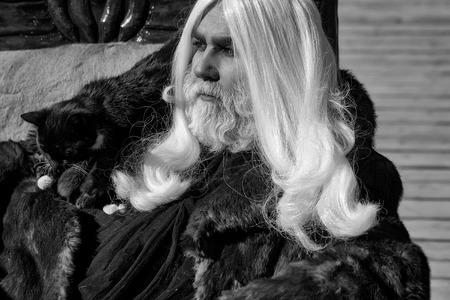 灰色の背景に毛皮のコートで肩に黒猫と長い銀髪のひげを持つドルイド老人