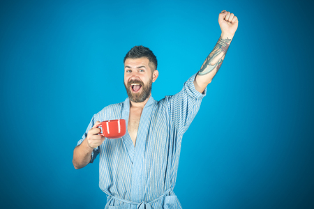 Man drink morning coffee or tea. Bearded hipster with red milk cup. Refreshment and energy, break. Happy guy with mulled wine on blue background. Perfect morning with coffee. Imagens