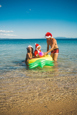 New year man, girl with small boy. Santa child, parents at Christmas. Xmas party celebration, fathers and mothers day. Christmas happy family on pineapple mattress in water. Winter holiday vacation. Stock Photo