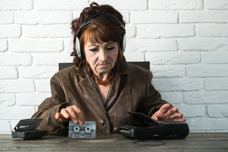 Old school music player, radio. Spy and operator. Granny dj in headset with cassette player. Old woman with cassette recorder listen music in headphones. Audio book and new technology, education. Stock Photo