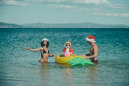 Christmas happy family on pineapple mattress in water. Winter holiday vacation. New year man, girl with small boy. Xmas party celebration, fathers and mothers day. Santa child, parents at Christmas.