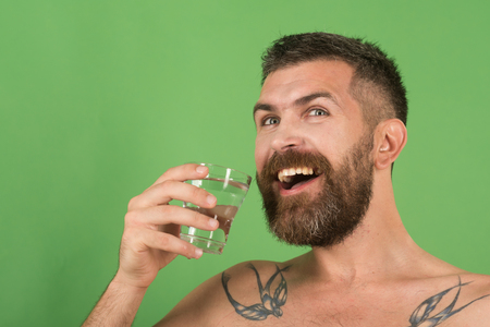 Life source and healthcare. Happy hipster drink clean healthy water, refreshing. Hangover and thirst. Man with long beard hold water glass on green background. Health and dieting.