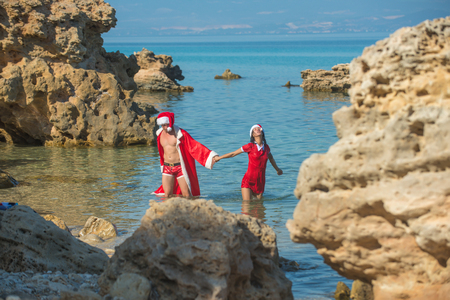 Christmas couple in red at beach. Couple in love of happy man and woman in water. New year girl and guy as santa. Xmas party celebration and activity. Winter holiday and vacation. Foto de archivo