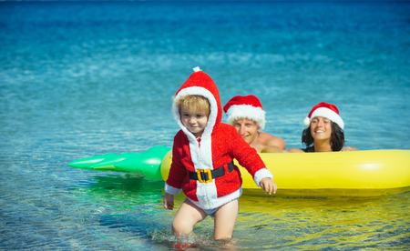 Winter holiday vacation. Christmas happy family on pineapple mattress in water. Xmas party celebration, fathers and mothers day. Santa child, parents at Christmas. New year man, girl with small boy.