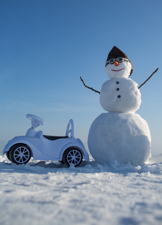 New year snowman in pilot hat and glasses. Happy holiday celebration. Christmas and transportation. Snowman in winter with toy car, travel and vaction. Xmas or christmas decoration, aviation.