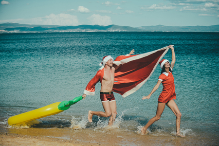 christmas couple in love in red santa claus hat at sea or ocean water beach with pineapple mattress, summer and winter vacation, new year holiday and party celebration, love and relations