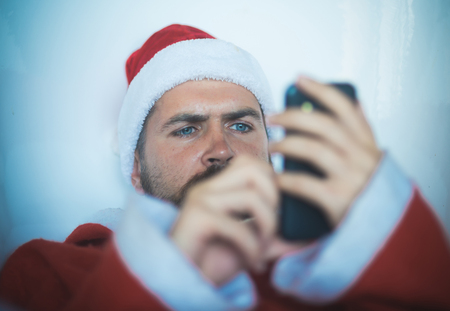 Expectation, love and betrayal, Christmas man or hipster santa with beard communicating on mobile phone, home alone Stock Photo