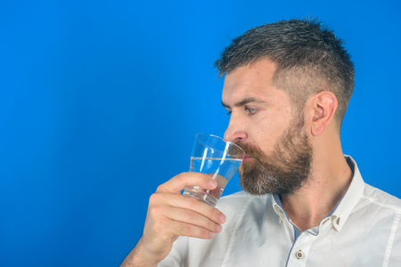 Man with long beard hold water glass on blue background. Hipster drink clean healthy water, refreshing. Health and dieting. Hangover and thirst. Life source and healthcare, copy space Imagens