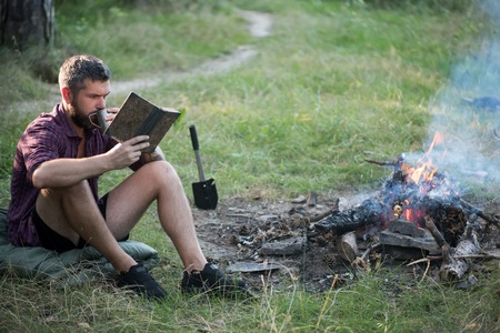 Sustainable education, environment concept. Camping, hiking, lifestyle. Man traveler read and drink at campfire flame. Hipster hiker with book and mug at bonfire in forest. Summer vacation, activity.