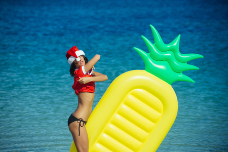 Santa claus sexy girl in red Christmas costume. Winter holiday vacation. New year woman swim at beach. Xmas party celebration. Christmas woman with pineapple mattress in water.