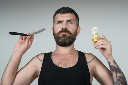 男はかみそりと剃毛ブラシでひげと口ひげをカットしました。理髪店の深刻なヒップスター、新しい技術。あごひげ男の散髪、考古学。床屋と美容