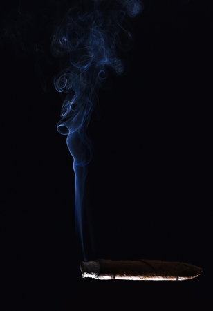 cigarette with blue smoke on black background, bad habits and addiction, drug and unhealthy lifestyle Stock Photo