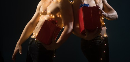Twins santa with muscular body in garland. New year strip and gifts for adults. Call boys or sexy athlete men at xmas. Young men hold present for girls. Christmas party and sex games. Imagens