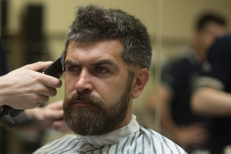 Fashion and beauty, innovation. Barber and hairdresser. Haircut of bearded man, archaism. Man cut long beard and mustache with trimmer razor. Hipster with serious face in barbershop, new technology.