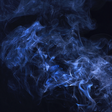 Blue smoke on black background. Spirit and ghost, miracle. Blue ink in freeze motion, powder splatted explosion. Smoking cloud backdrop. Abstract background with smoke. Stock Photo