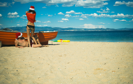 Couple in love of happy man and woman, travel. Xmas party celebration. New year girl and guy as santa. Winter holiday and vacation. Christmas couple in red at beach boat, copy space