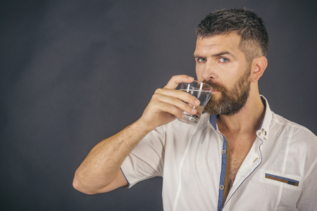 Hipster drink clean healthy water, refreshing. Man with long beard hold water glass on grey background. Health and dieting. Hangover and thirst. Life source and healthcare, copy space Imagens - 92124979