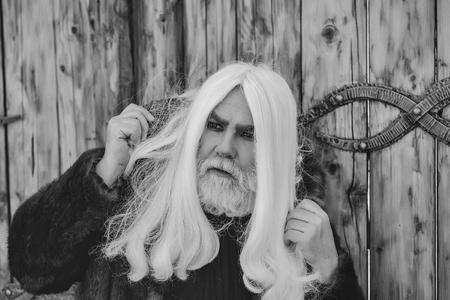 長い灰色の髪と鉄の装飾と木製の背景に屋外の深刻な顔にひげを持つドルイド老人