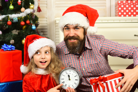 Happy family celebrate new year and Christmas. Father and child with present box and clock. Winter holiday and New year. Father and daughter in santa hat at Christmas tree. Xmas party celebration.