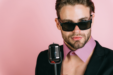 man in glasses sing in microphone. dj young man on pink background, radio. Music, look and retro style, freak. singer with stylish retro hair, show business. Stock Photo