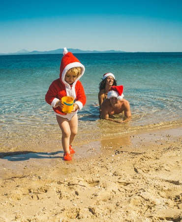Christmas happy family in water. Winter holiday vacation. Xmas party celebration, fathers and mothers day. Santa child, parents at Christmas. New year man, girl with small boy.