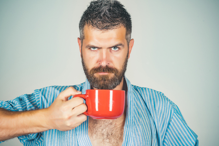 serious guy with mulled wine on grey background. Man drink morning coffee or tea. Refreshment and energy, break. Bearded hipster with red milk cup. Perfect morning with coffee. Standard-Bild