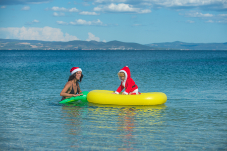 Santa child, mother at Christmas. Xmas party celebration, mothers day. Winter holiday vacation. New year girl with small boy. Christmas happy family on pineapple mattress in water.