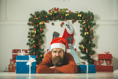 christmas man with beard on sad face in red santa claus hat near present box at new year decoration fireplace, winter holiday celebration, boxing day