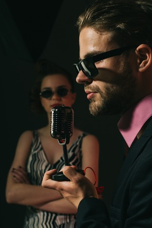 Music and love. Couple in love in glasses sing in microphone. Beauty and vintage fashion, music band. Pinup girl and man sing karaoke, radio. Singer man and woman with retro hair and makeup.