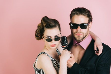 Singer man and woman with retro hair and makeup. Beauty and vintage fashion, music band. Music and love. Pinup girl and man on pink background, radio. Couple in love in glasses sing in microphone.