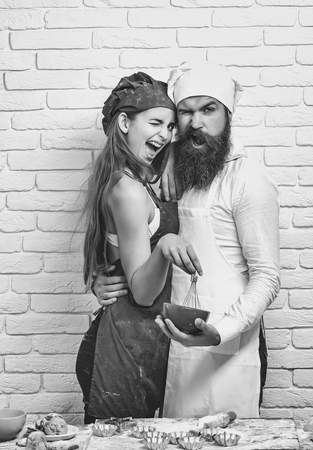 Bearded man, handsome cook or baker and pretty girl or beautiful woman in red apron messy with flour and whisk in bowl on white kitchen wall