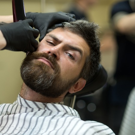 Fashion and beauty, innovation. Haircut of bearded man, archaism. Man cut long beard and mustache with trimmer razor. Barber and hairdresser. Hipster with serious face in barbershop, new technology. 免版税图像