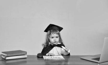 黒い正方形の帽子と灰色の背景にコンピュータマウスのノートブックや日記の近くの運動本のマーカーで描く木製の学校の机に座ってかわいい男の子の小さな子供 写真素材 - 92123397