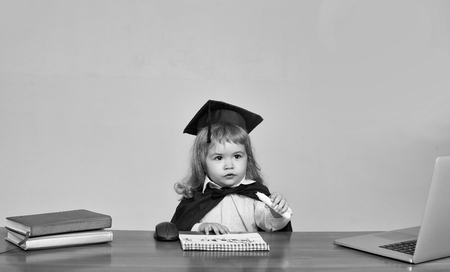 Cute boy small child in black squared hat and academic gown sitting at wooden school desk drawing by marker in exercise book near computer mouse notebook and diaries on gray background Reklamní fotografie