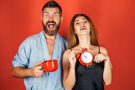 Refreshment and energy, time. man and girl with mulled wine on red. Perfect morning with coffee. couple in love drink morning coffee or tea. family of man and woman with cup and alarm clock.