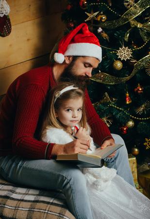 Xmas feestviering, vaders dag. Wintervakantie en vakantie. Kerstmis gelukkig kind en vader gelezen boek. Nieuwjaar klein meisje en man, sprookje. Kerstman jongen en bebaarde man op kerstboom.
