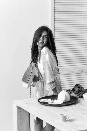 Happy pretty girl or beautiful woman, housewife, with long brunette hair in sexy dressing gown smiling with electric iron in hand for ironing clothes on white wall. Housework and housekeeping Stock Photo