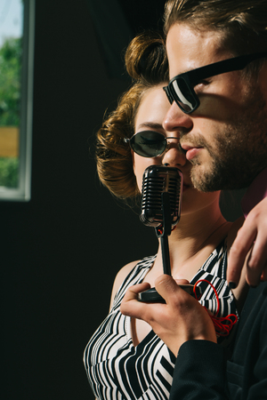 Pinup girl and man sing karaoke, radio. Singer man and woman with retro hair and makeup. Beauty and vintage fashion, music band. Couple in love in glasses sing in microphone. Music and love.