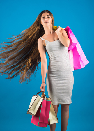 Woman with happy face hold shopping bag near blue wall. Girl with long hair hold present pack, cyber Monday. Fashion and beauty, shopaholic girl. Shopping and sale. Black Friday, holiday celebration.