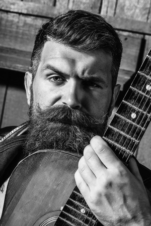 Frown bearded man with beard moustache and gray hair stylish hipster male with guitar outdoors on wooden background