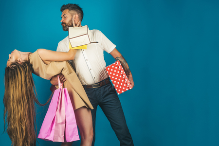Shopping and sale. Girl and bearded man hold present pack, cyber Monday. Fashion shopaholic couple. Black Friday, happy holiday, relations. Couple in love hold shopping bag near blue wall, copy space