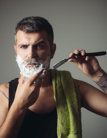 男はかみそりと剃毛ブラシでひげと口ひげをカットしました。理髪店の深刻なヒップスター、新しい技術。床屋と美容師あごひげ男の散髪、考古学