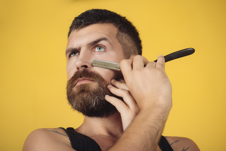 Fashion and beauty, innovation. Barber and hairdresser. Haircut of bearded man, archaism. Man cut beard and mustache with razor. Serious hipster in barbershop, new technology. 스톡 콘텐츠