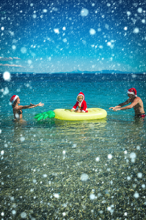 new year christmas snow concept Christmas happy family on pineapple mattress in water. New year man, girl with small boy. Santa child, parents at Christmas. Xmas party celebration, fathers and mothers Stock Photo