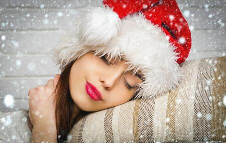 christmas new year snow concept Christmas woman sleep at midnight. Santa claus girl in red hat. holiday and celebration. Xmas and party. New year sleepy girl relax.