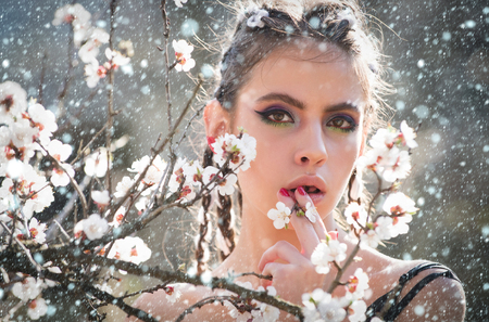 new year christmas snow concept girl and flowers. pretty woman eating white cherry or apricot spring flower blooming, has fashionable makeup on face and stylish hair sunny outdoor natural background Stockfoto