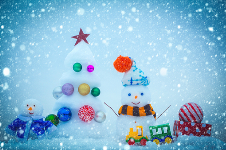 new year christmas snow concept Snow sculptures on blue background. Snowmen with smiley faces in clothing. Christmas tree with ball decorations, toy train and present box. xmas and new year. Winter Stock Photo